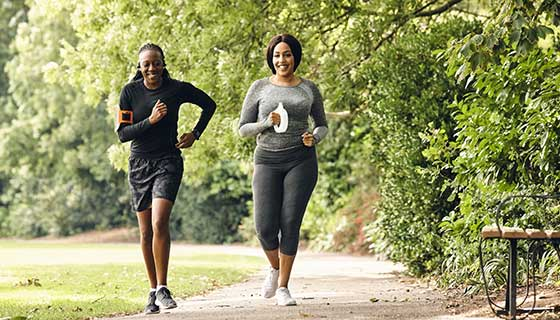 Two women jogging together on an outdoor track