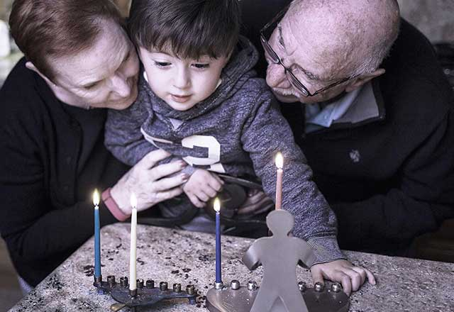 Grandparents gather around the menorah with their grandson.
