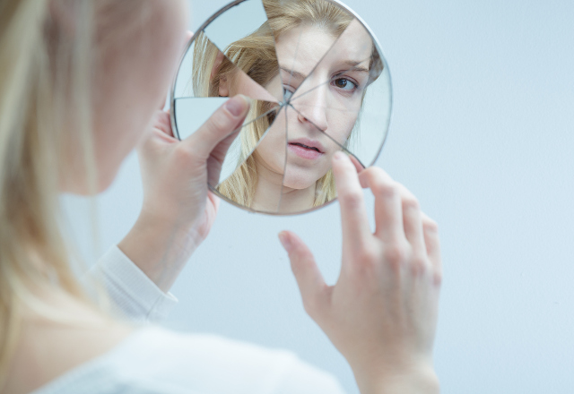 A woman looking in a broken mirror.