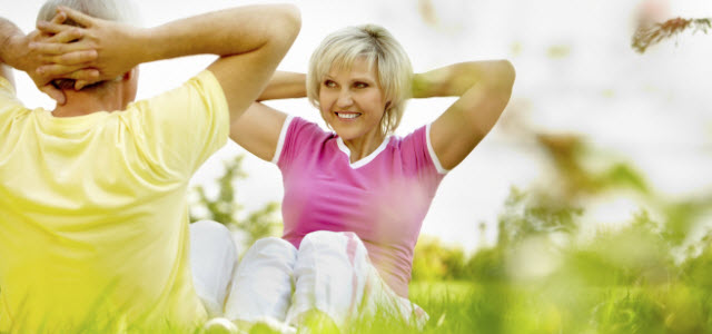 older couple doing sit-ups outside