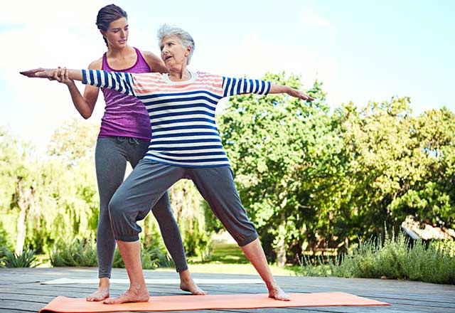 A yoga instructor assists a senior with her posture.