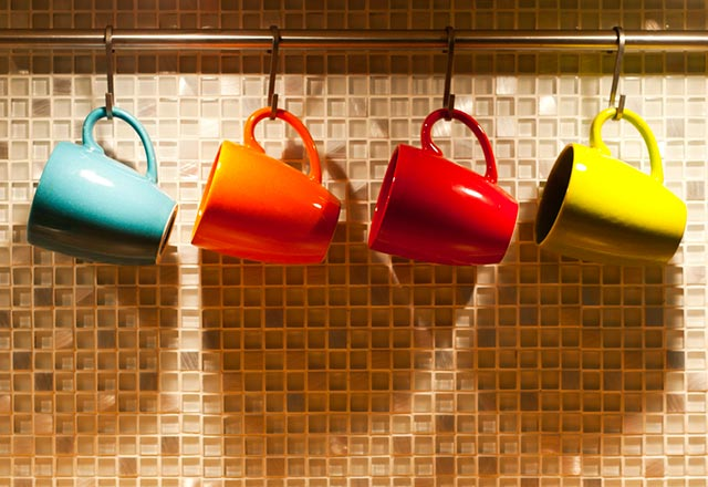 A collection of colorful coffee mugs hang beneath a cabinet.