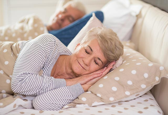 A senior couple asleep in bed.