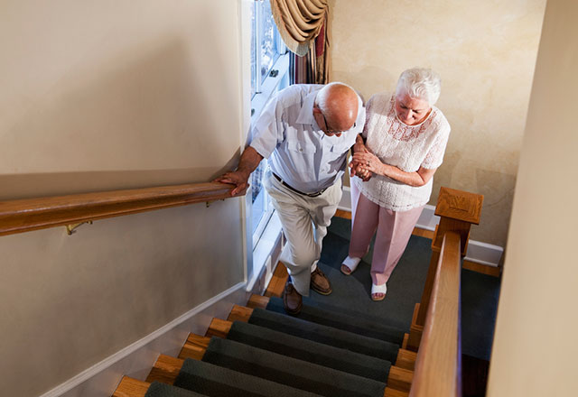 A senior woman helps her husband go up the stairs.