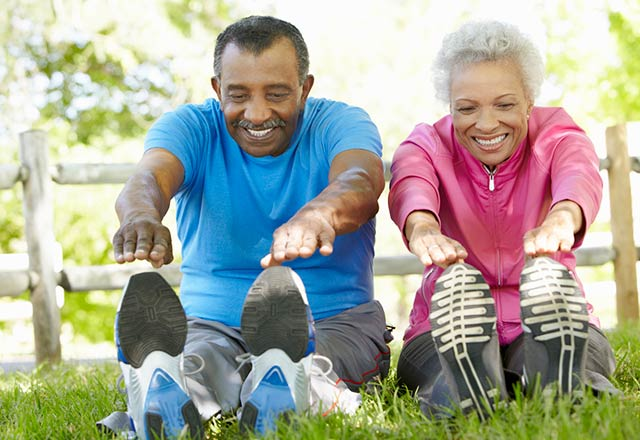An active senior couple stretch before going on a jog.