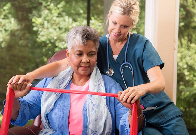 A physical therapist assists a senior woman as she exercises using a resistance band.