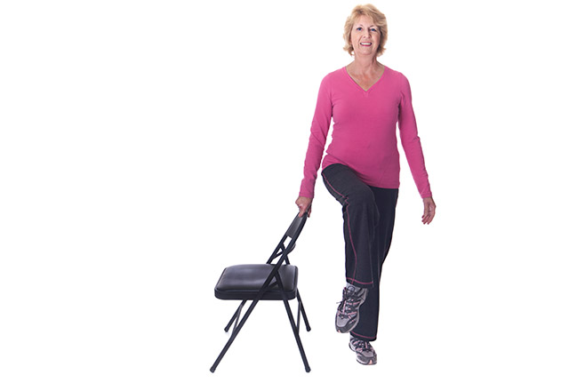 A senior woman exercises using a chair for support.