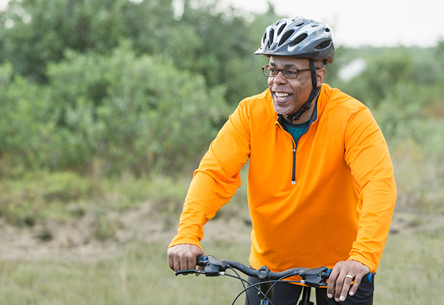 Older gentleman riding a bike through a wooded trail.