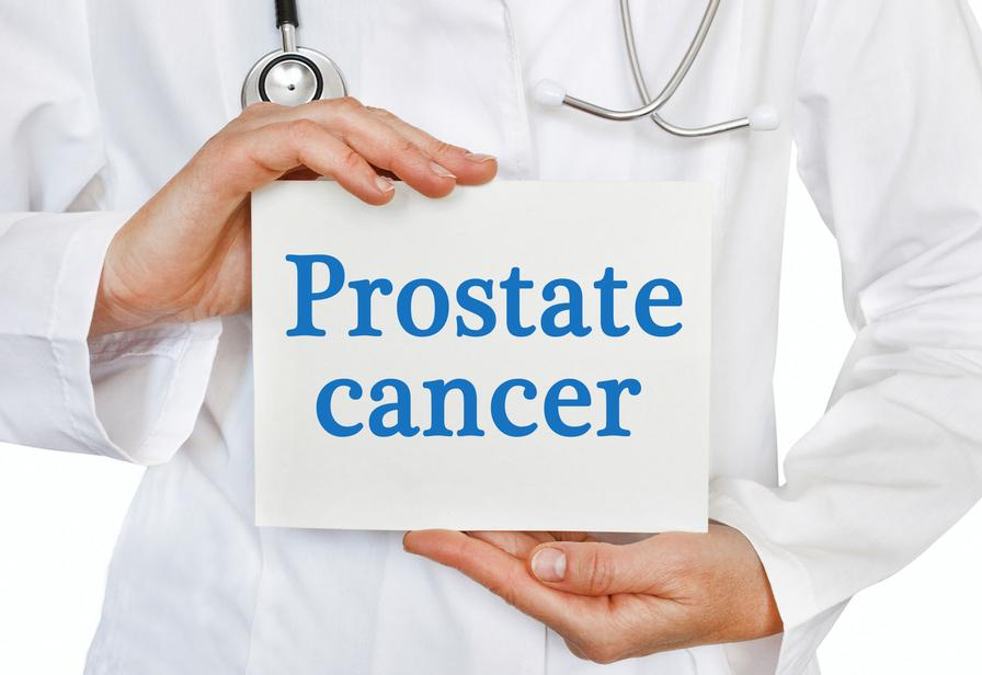 "Physician holding a piece of paper that says, ""Prostate cancer""."