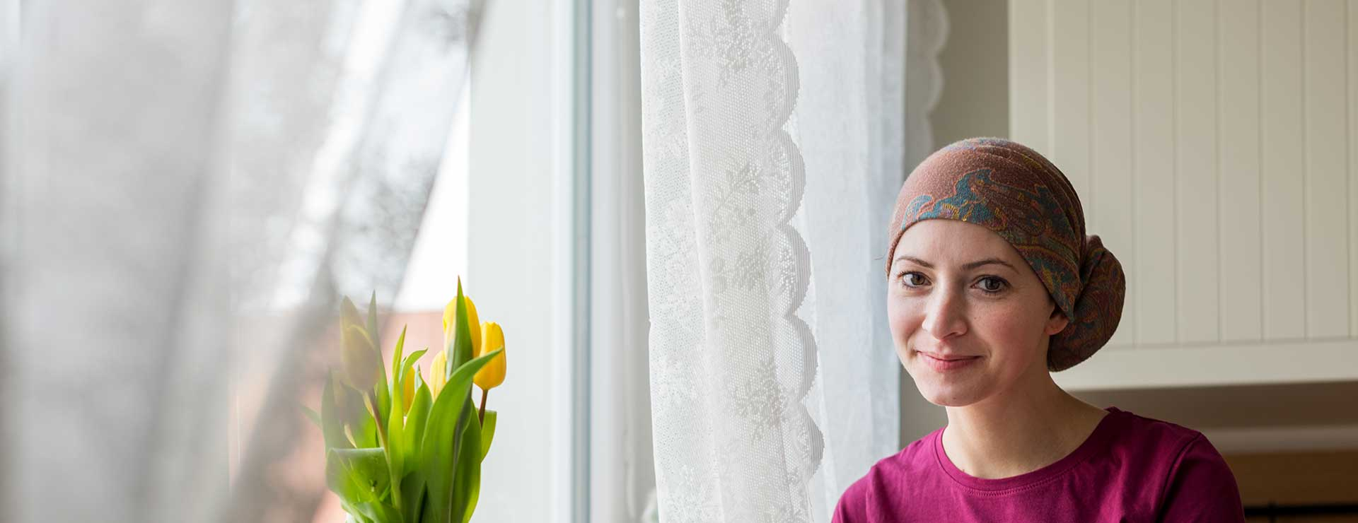 A young cancer patient sits in front of a window.