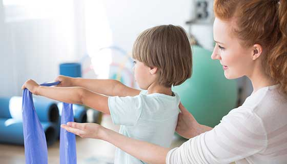 Physical therapist working with a child to correct scoliosis