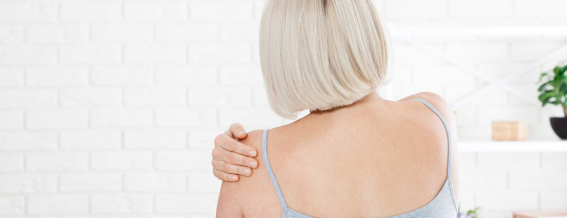 Woman holder her shoulder in pain