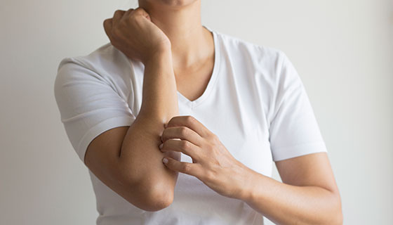 A woman itches her arm, below the elbow.