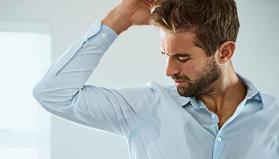 A man sweats through his shirt.