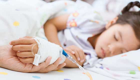 A young child sleeps in a hospital bed while a parent holds their hand.