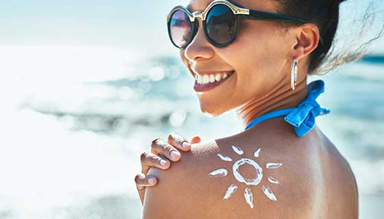 woman smiles with sun drawn in lotion on shoulder