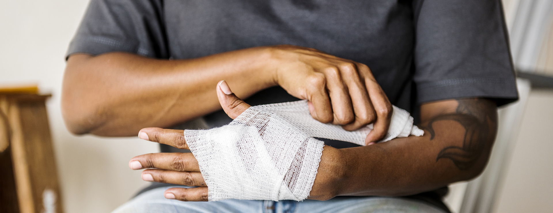 A person carefully wraps their arm in gauze.