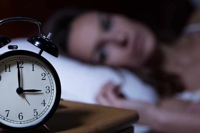 Woman stares at her alarm clock in the middle of the night.