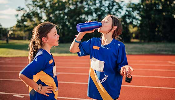 Two girls on a track field drinking water after training