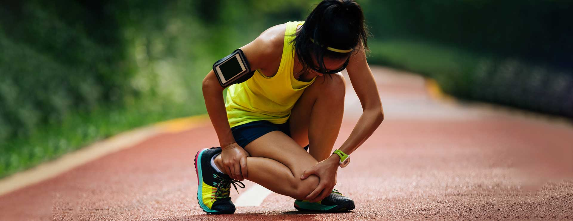 woman runner holding her knee in pain