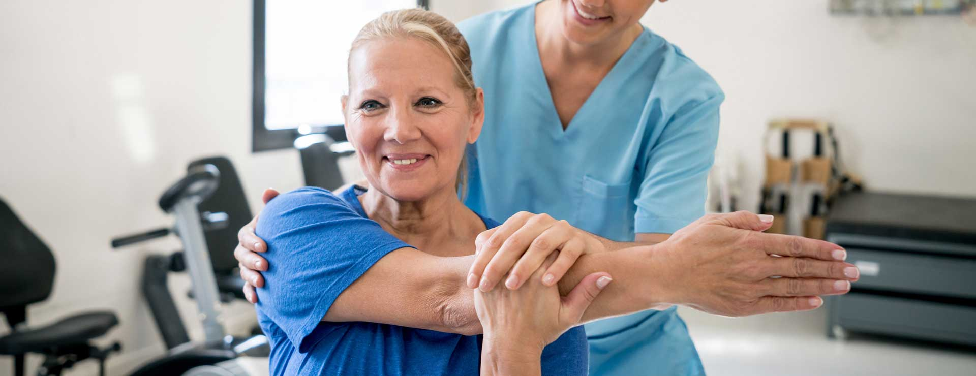 Physical therapist holding senior patient while she stretches her shoulder