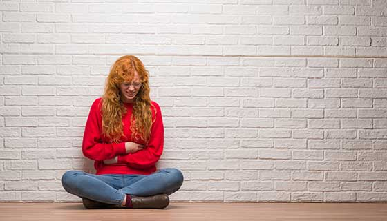 A young woman sits against a wall, clutching her stomach.