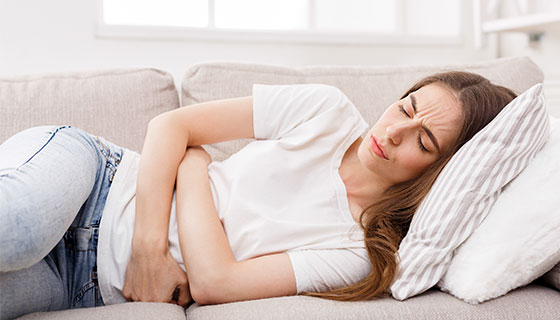 woman clutching stomach on sofa