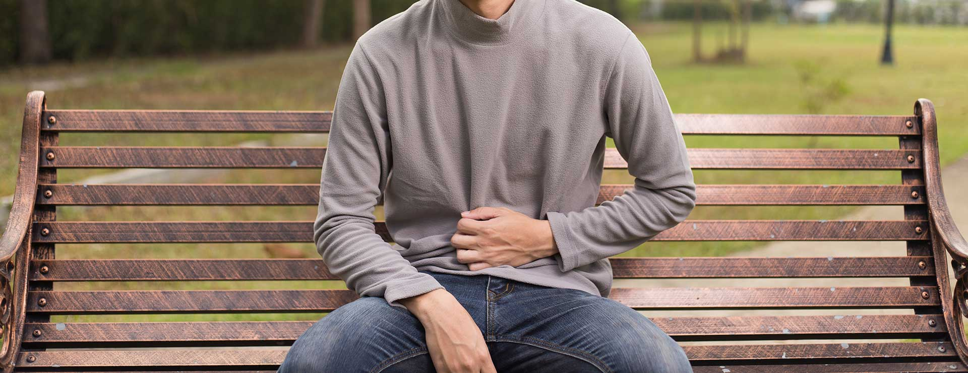 A young man sits on a bench outside, holding his stomach in pain.