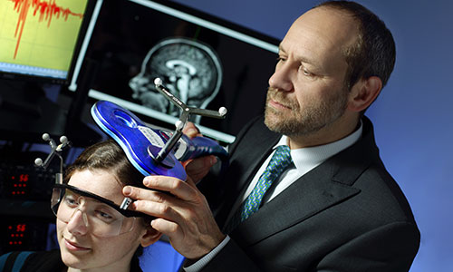 Dr. Pablo Celnik demonstrates the use of noninvasive brain stimulation on a patient