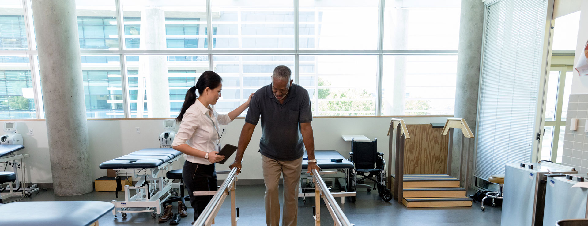 A physical therapist helps a man walk with the help of support bars.