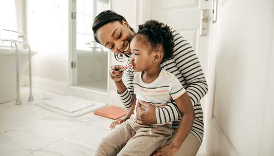 young mother helping child brush teeth