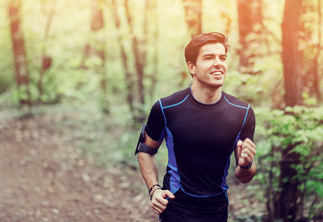 Young man running on a wooded trail