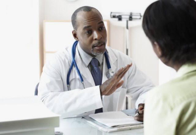male doctor speaking to female patient