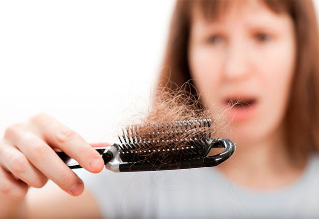 Woman looks frustratingly at hair loss on brush
