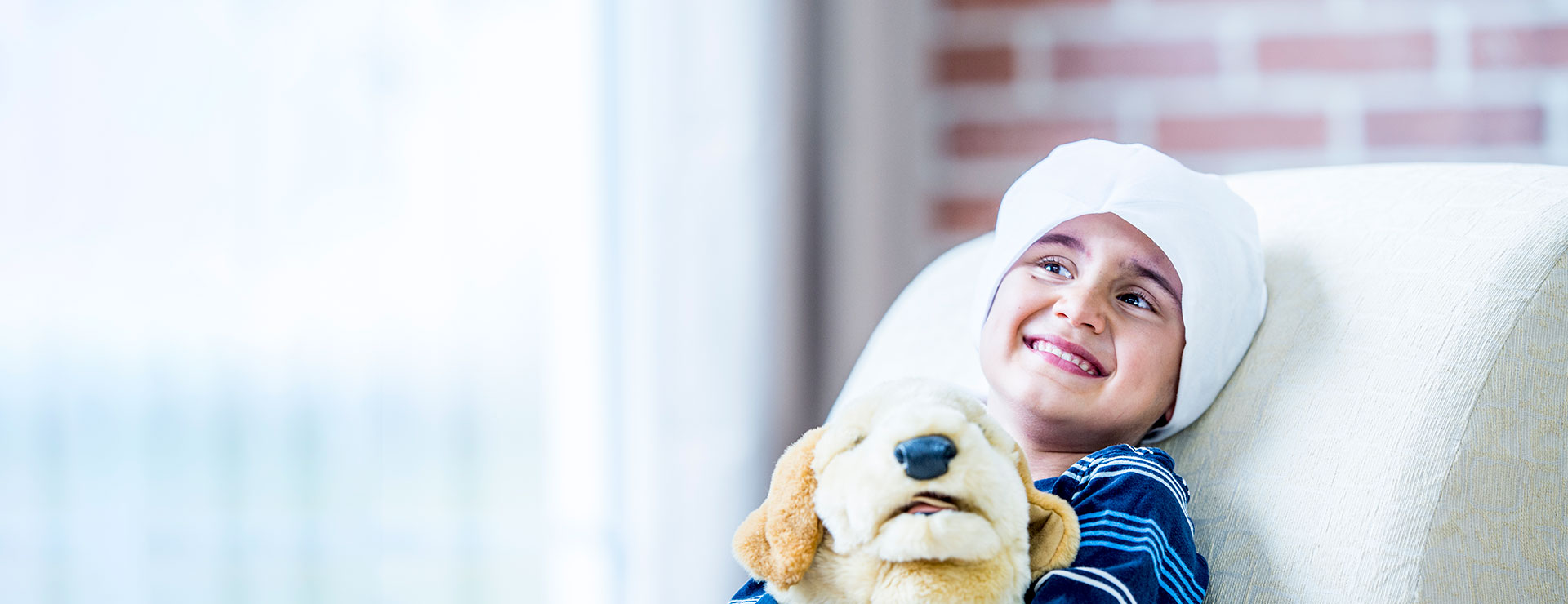 A young cancer patient holds a stuffed dog plush