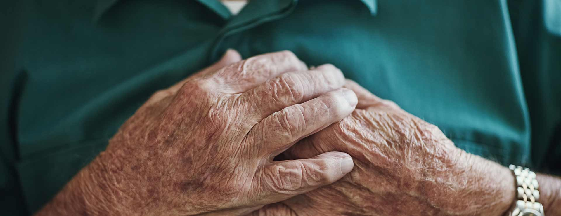 A senior man rests his hands on his chest.