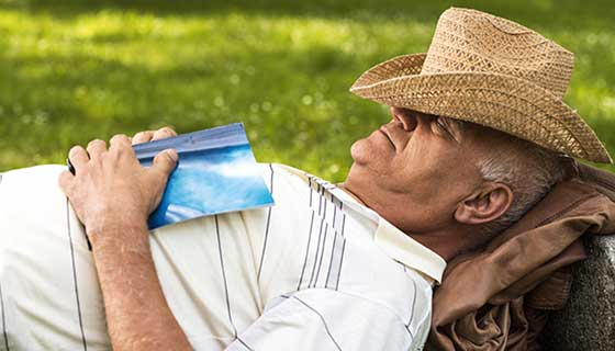 senior man with hat napping outdoors
