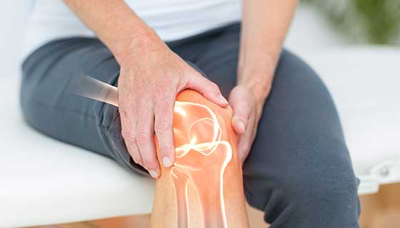 Woman holding knee in pain