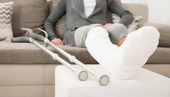 A person elevates their broken leg while sitting on the couch.