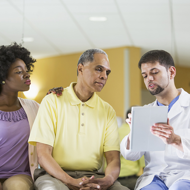 Male patient and his daughter listen to doctor's instructions