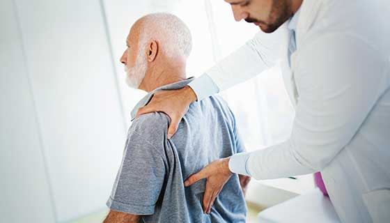 Doctor examining patient's lower back