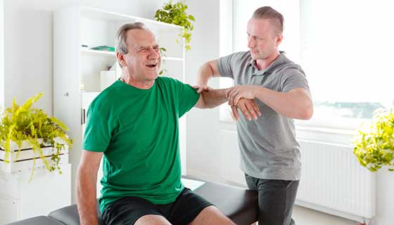 Physical therapist examining senior man's shoulder problem