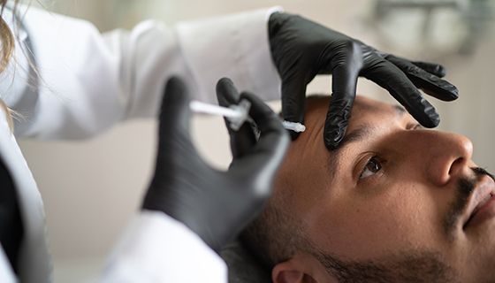 A man receives a botulinum toxin injection to his forehead.