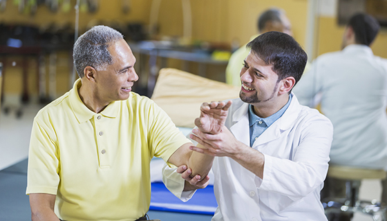 A doctor examines an older male patient's wrist.