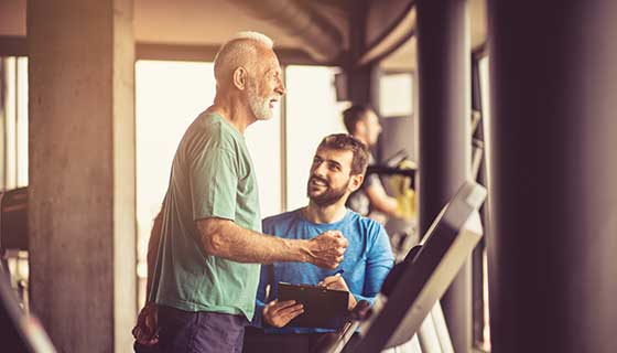 older man with trainer doing cardio