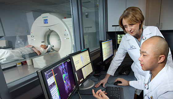 radiologist looking at CT scan