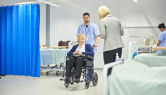 woman in wheelchair leaving hospital