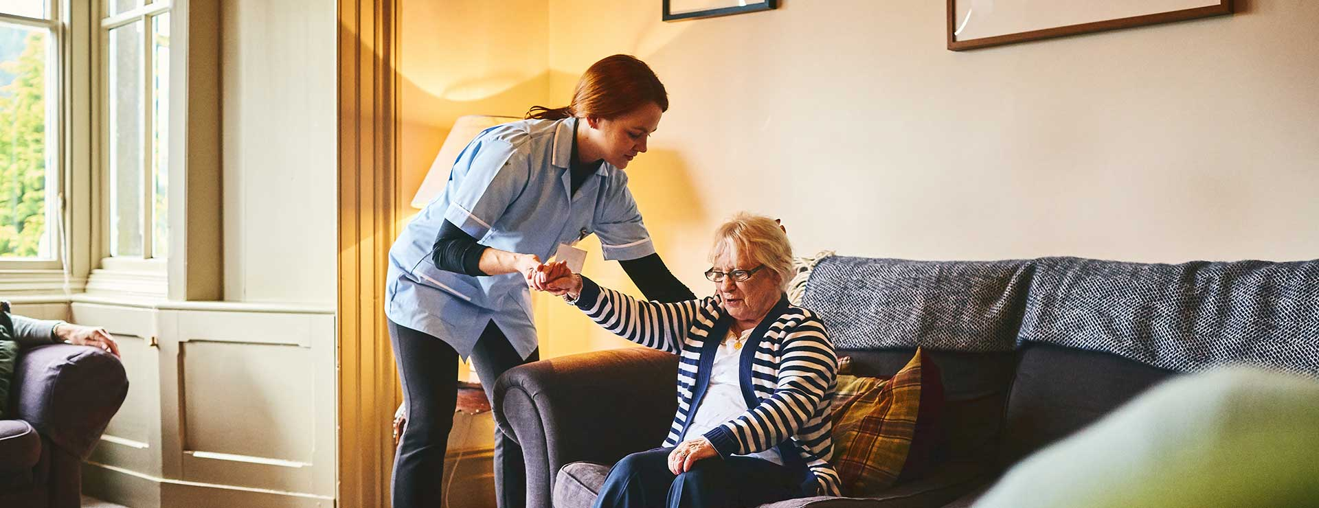 A caregiver helping woman off the couch