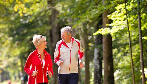A senior couple jogs outdoors.
