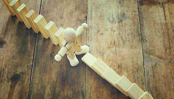 Wooden figure stopping falling dominos